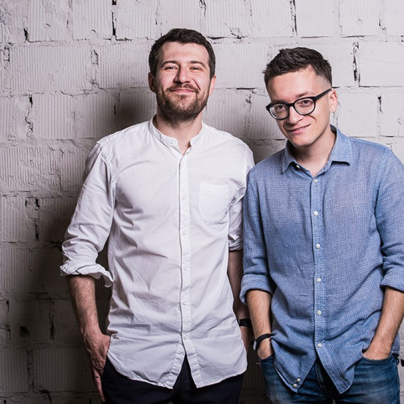 two-young-men-startupers-over-grey-brick-wall-PCL69T8.jpg